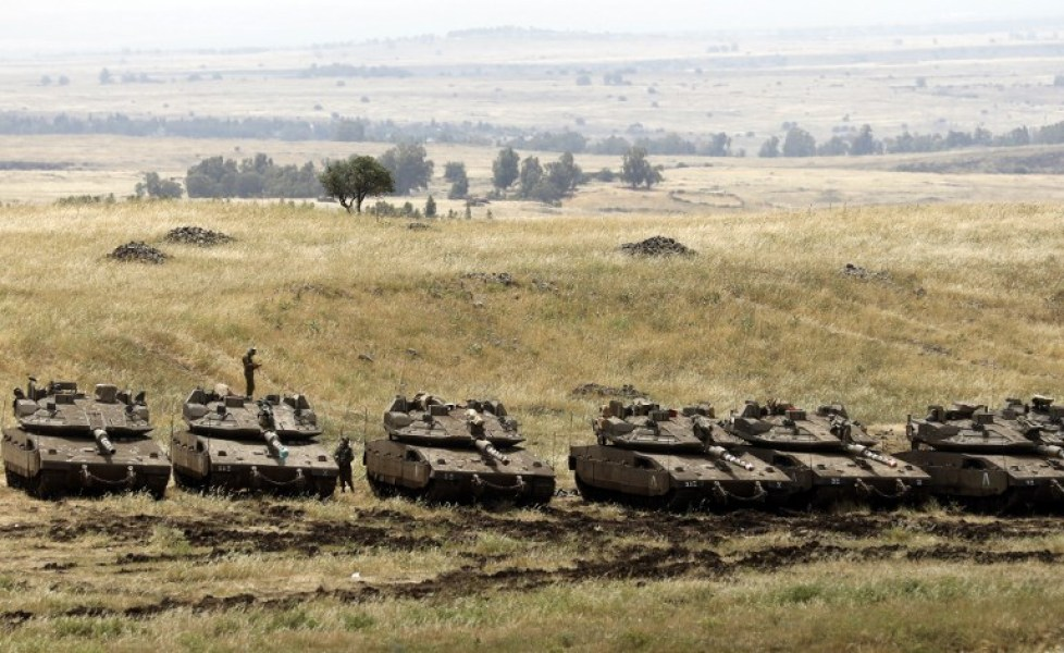 Israeli Merkava tanks and soldiers are seen in a deployment area near the Syrian border in the Israel-annexed Golan Heights on May 10, 2018. Israel's army said today it had carried out widespread raids against Iranian targets in Syria overnight after rocket fire towards its forces it blamed on Iran, marking a sharp escalation between the two enemies. Israel carried out the raids after it said around 20 rockets, either Fajr or Grad type, were fired from Syria at its forces in the occupied Golan Heights at around midnight.
