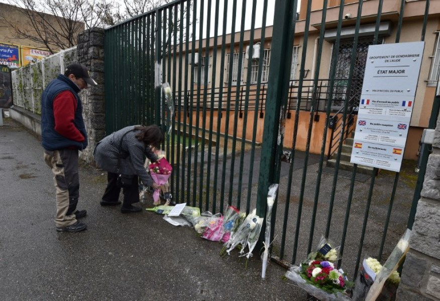 People lay flowers in front of the Gendarmerie Nationale in Carcassonne on March 24, 2018 in tribute to the gendarme killed after swapping himself for a hostage during an attack by a gunman who left a total of four people dead on March 23, 2018. Four people were killed on March 23 when a man claiming allegiance to the Islamic State group went on a shooting spree and held people hostage in a supermarket in Trebes, southwestern France before being shot dead by police. PASCAL PAVANI / AFP