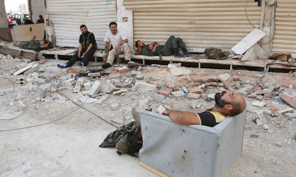 Syrian army soldiers rest in a street in the government-controlled part of the besieged town of Daraya on August 26, 2016, as thousands of rebel fighters and civilians prepared to evacuate under an accord struck a day earlier. An estimated 8,000 people remain in the town, despite a government siege lasting four years and regular regime bombardment.  Youssef KARWASHAN / AFP