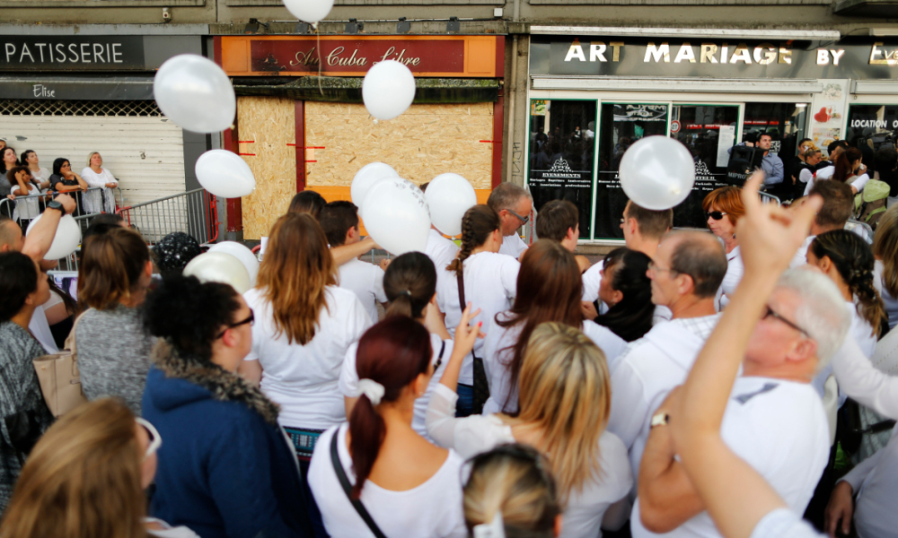"People hold white ballons as they gather in tribute to the victims in front of the ""Au Cuba Libre"" bar in Rouen, northwestern France, on August 11, 2016 after a fire sparked on August 6, 2016. A fire sparked by birthday cake candles tore through a bar in northern France on August 6, killing at least 13 people in the nation's deadliest blaze in over a decade, according to investigators.  CHARLY TRIBALLEAU / AFP"