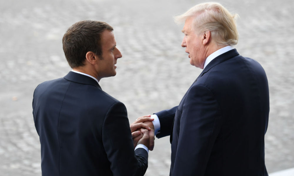 French President Emmanuel Macron (L) bids farewell to his US counterpart Donald Trump after the annual Bastille Day military parade on the Champs-Elysees avenue in Paris on July 14, 2017.
