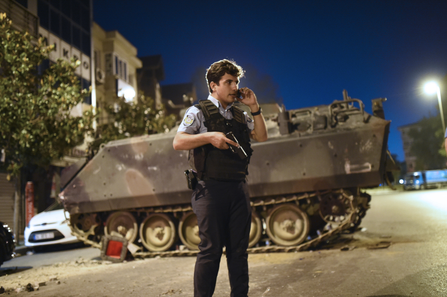 A Turkish police officer talks on a phone during clashes in Istanbul on July 16, 2016. At least 60 people have been killed and 336 detained in a night of violence across Turkey sparked when elements in the military staged an attempted coup, a senior Turkish official said. The majority of those killed were civilians and most of those detained are soldiers
