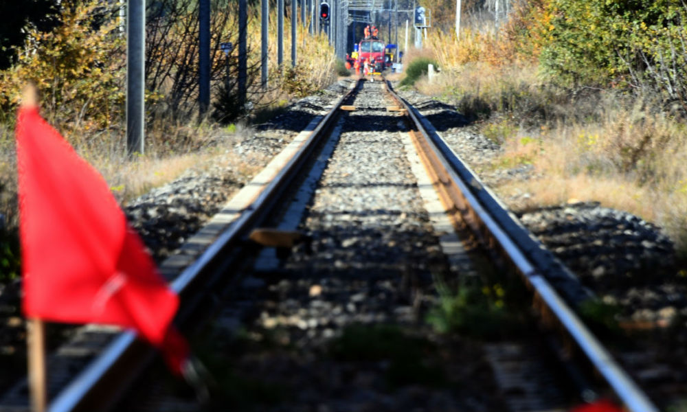 A red flag is displayed on the railway between Millas and Saint-feliu-d'Avallas, on December 16, 2017 as French gendarmes and employees of the National society of French railways (SNCF) investigate at the level crossing, two days after some children were involved in an accident between a regional TER train and a school bus.