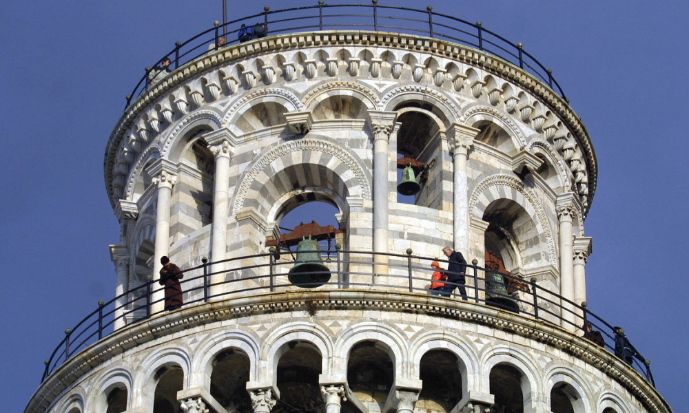 "A group of tourists walks on the top of the leaning tower of Pisa 15 December 2001, the day of the official opening to the public after an 11-year closure for restoration after engineers judged the tower too fragile and unstable. For most of the past decade, the 54.5-meter tall marble monument was girdled in steel and anchored by a pair of slender steel ""suspenders'' running across the surrounding square. By using hundreds of tons of counterweights at the base and extracting soil from under the foundation, engineers guided the tower back to where it was in 1838. AFP PHOTO ALBERTO PIZZOLI ALBERTO PIZZOLI / AFP"