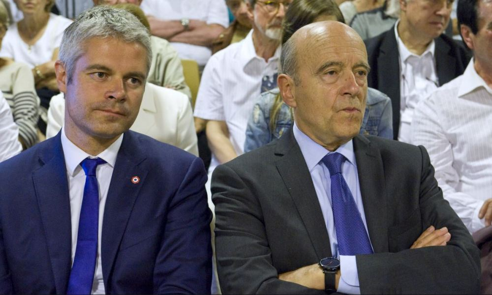 Mayor of Bordeaux and presidential candidate of the opposition Les Republicains (LR) party for the French presidential elections in 2017 Alain Juppe (R) sits next to French President of Rhone-Alpes-Auvergne region Laurent Wauquiez during a campaign meeting in Blavozy on June 22, 2016.  Thierry Zoccolan / AFP