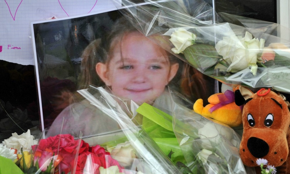 (FILES) This file photo taken on September 29, 2013 shows a picture of five-year-old Fiona put among flowers, toys and messages left outside the house where she used to live in Clermont-Ferrand. The mother and mother's former partner of late Fiona, disappeared in May 2013 in Clermont-Ferrand, will appear before the criminal court in Puy-de-Dôme, on November 14, 2016. THIERRY ZOCCOLAN / AFP