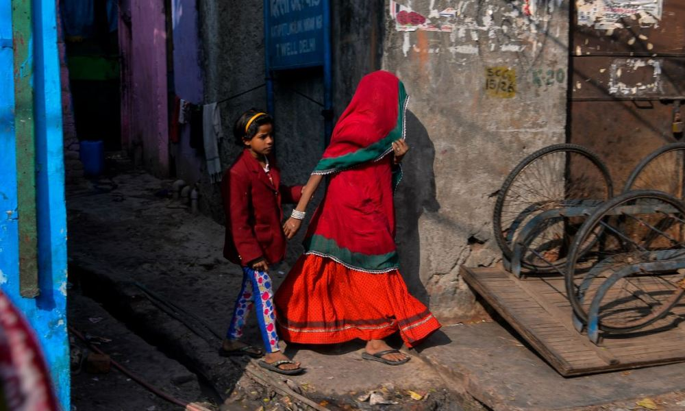 A young Indian girl holds her mother's hand as she walks out of an alley in the Kathputli Colony in New Delhi on December 20, 2016.