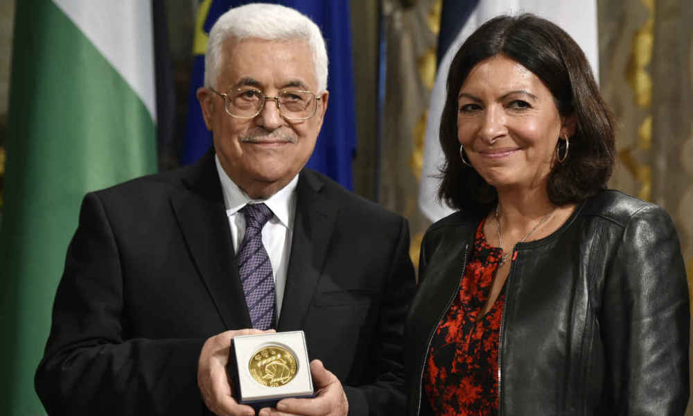 Palestinian Authority president Mahmoud Abbas (L) poses next to Paris' mayor Anne Hidalgo after receiving the medal of Paris during a ceremony marking the International Day of Peace on September 21, 2015 at Paris' city hall . AFP PHOTO / DOMINIQUE FAGET