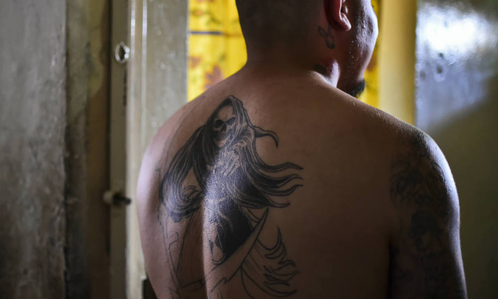 "An inmate tattooed with ""The Santa Muerte"" poses at the mixed-sex prison of Tulancingo, Hidalgo State, Mexico, on June 29, 2016. Men and women, 549 in total, live together in common spaces at the prison of Tulancingo."