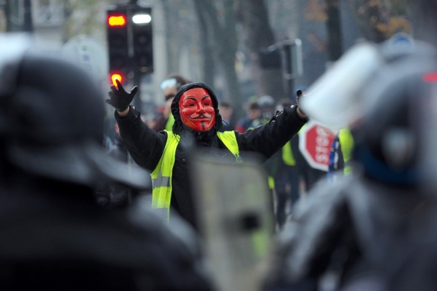 "A yellow vest (Gilets jaunes) protester wearing a Guy Fawkes mask gestures in front of French riot police during a demonstration against rising oil prices and living costs in Tours, central France on December 1, 2018. The ""yellow vest"" or ""Gilets jaunes"" movement is named after the high-visibility jackets which motorists are required to carry in their cars. The movement, organised through social media, has steadfastly refused to align with any political party or trade union and includes many pensioners and has been most active in small urban and rural areas where it has blocked roads, closed motorway toll booths, and even walled up the entrance to tax offices. GUILLAUME SOUVANT / AFP"