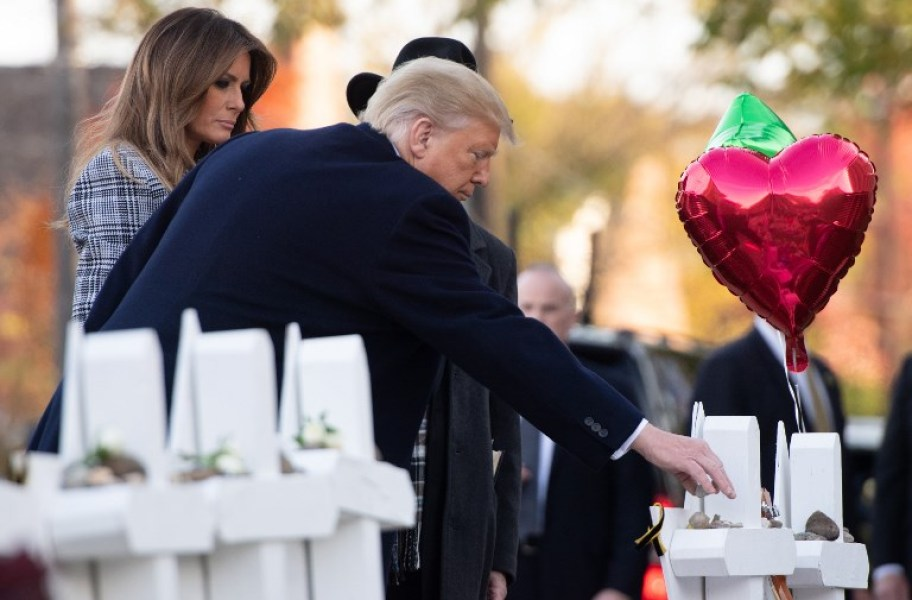 "US President Donald Trump and First Lady Melania Trump, alongside Rabbi Jeffrey Myers, place stones and flowers on a memorial as they pay their respects at the Tree of Life Synagogue following last weekend's shooting in Pittsburgh, Pennsylvania, October 30, 2018. Scores of protesters took to the streets of Pittsburgh to denounce a visit by US President Donald Trump in the wake of a mass shooting at a synagogue that left 11 people dead. Demonstrators gathered near the Tree of Life synagogue, where the shooting took place, holding signs that read ""President Hate, Leave Our State!"" and ""Trump, Renounce White Nationalism Now."" SAUL LOEB / AFP"