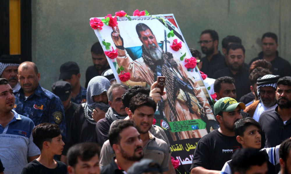 Iraqi mourners hold a portrait of Abu Tahsin al-Salhi, a veteran sniper from the Hashed al-Shaabi (Popular Mobilisation units) who boasted about killing at least 320 Islamic State (IS) group fighters, during his funeral on September 30, 2017 in the southern city of Basra. According to Ahmad al-Assadi, Hashed al-Shaabi's spokesman, Abu Tahsin fell a day earlier during the battle of Hawija. HAIDAR MOHAMMED ALI / AFP