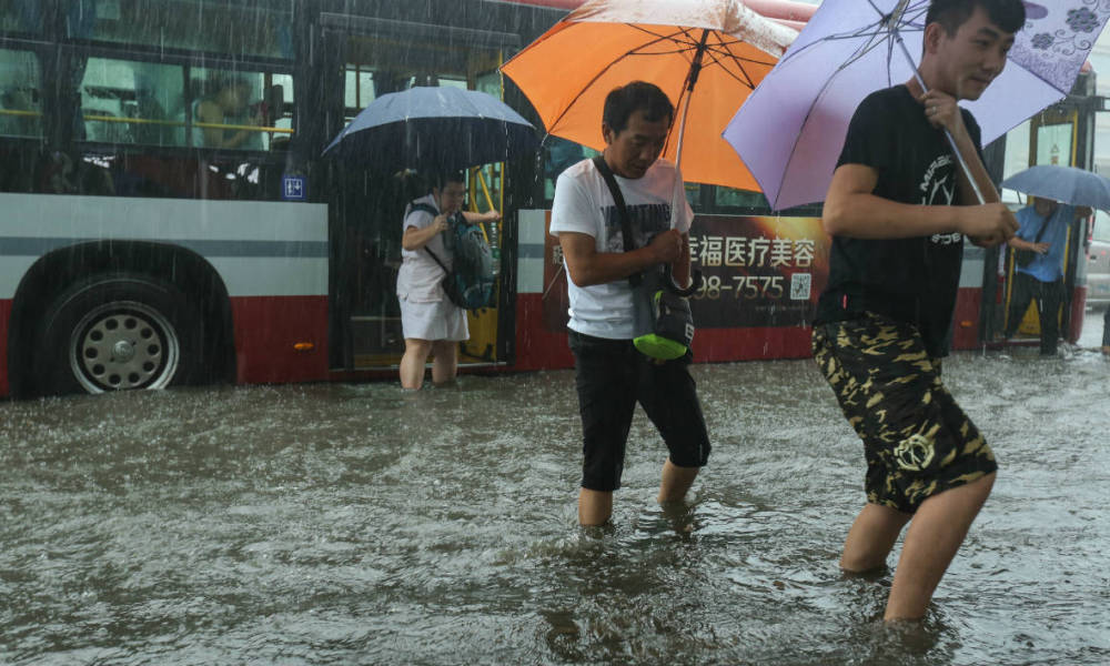 Commuters wade through water after getting off a bus in a flooded street in Beijing on July 20, 2016. Some areas and streets in Beijing have started to flood over due to heavy rain.