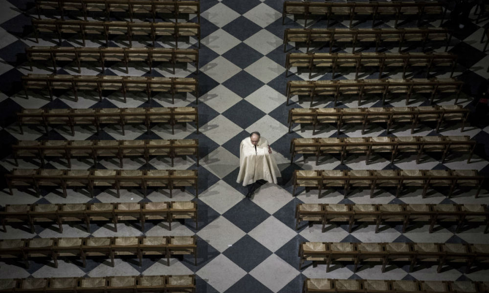 A priest walks along benches during a ceremony held to present to to faithfuls the Crown of Thorns -a relic of the passion of Christ- at the Notre-Dame Cathedral in Paris on April 14, 2017.  Philippe Lopez / AFP