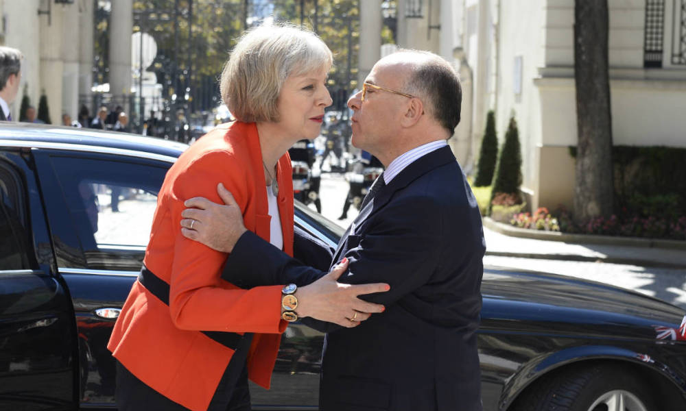 French Interior Minister Bernard Cazeneuve (R) shakes hands with British Home Secretary Theresa May as she arrives to attend a meeting with Union European Interior ministers in Paris, on August 29, 2015, days after a shooting occurred on board of an Amsterdam-Paris Thalys train.