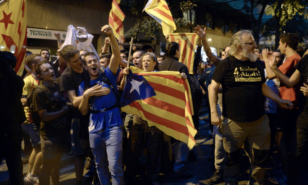 Pro-referendum demonstrators protest in front of Spanish National Police officers during a demonstration near the Economy headquarters of Catalonia's regional government in Barcelona on September 20, 2017.