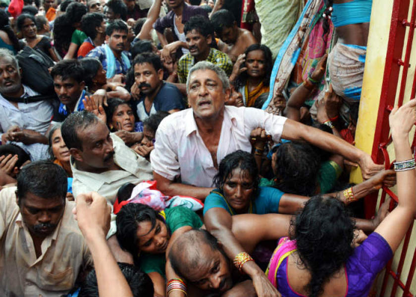 "Indian devotees gather after a stampede at a religious festival in Godavari in the Rajahmundry district some 200 kms north-east of Hyderabad on July 14, 2015. The death toll from a stampede July 14, 2015, on the banks of a holy river in southern India has risen to 27, the state government said. ""Twenty-seven people have now been confirmed dead in the stampede and another 29 are injured,"" a spokesman for Andhra Pradesh's Chief Minister Chandrababu Naidu said after police earlier put the number of dead at five. AFP PHOTO / STR"