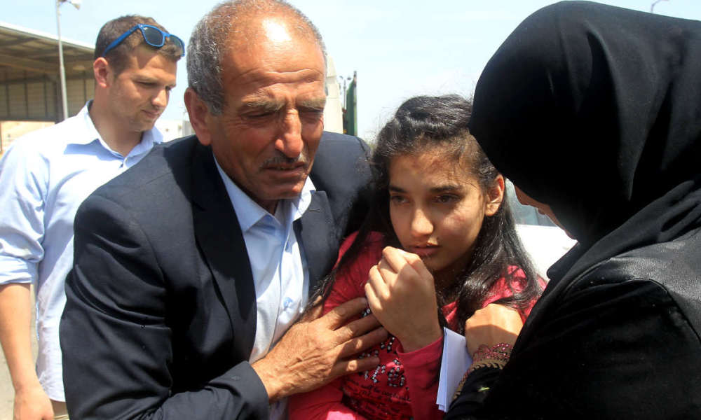 The parents of Palestinian Dima al-Wawi, 12, who is believed to be the youngest female detained by Israel, greet her in the West Bank city of Tulkarem, upon her release from Israeli prison on April 24, 2016.  JAAFAR ASHTIYEH / AFP