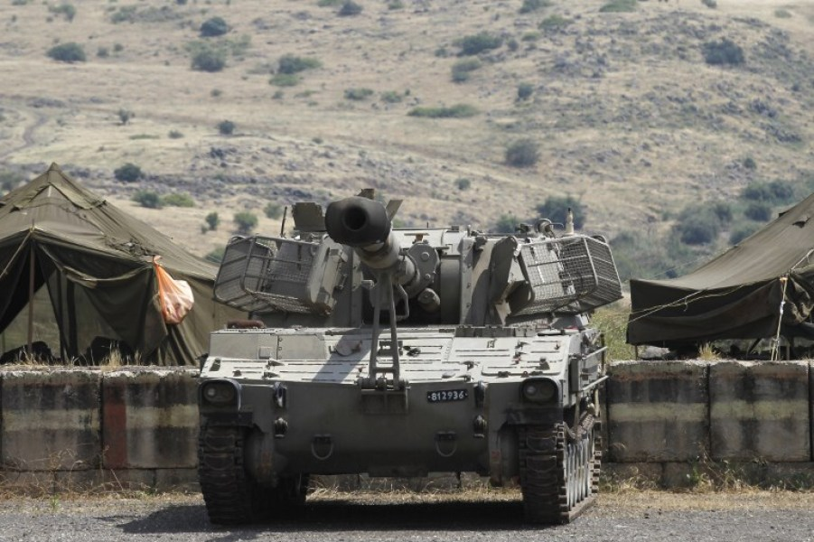 """An Israeli artillery unit takes position near the Syrian border in the Israeli-annexed Golan Heights on May 9, 2018. The Israeli-occupied section of the Golan Heights was placed on high alert due to """"irregular activity by Iranian forces"""" across the demarcation line in Syria. JALAA MAREY / AFP"""