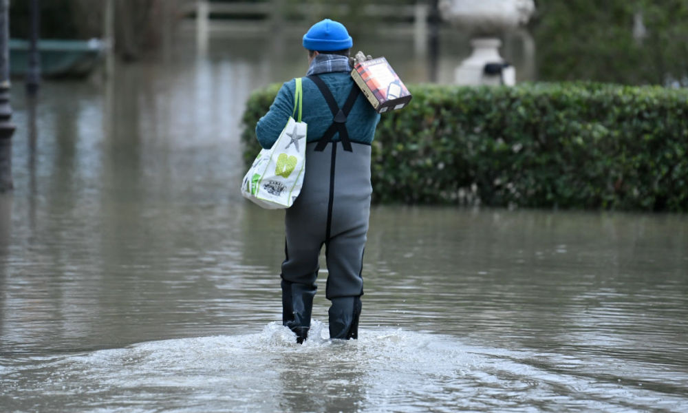 A local resident wearing waterproof pants carries boxed wine down a flooded street on the Seine river in Villennes-sur-Seine, west of Paris, on January 29, 2018. The swollen Seine peaked on January 29 at more than four metres above its normal level, leaving a lengthy mop-up job for Parisians after days of rising waters that have put the soggy city on alert.  STEPHANE DE SAKUTIN / AFP