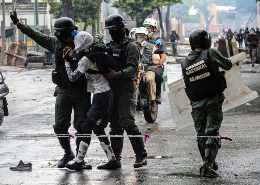 An anti-government activist is arrested during clashes in Caracas on July 28, 2017. Protesters took over streets in Caracas on Friday in a show of defiance to President Nicolas Maduro, as the crisis gripping Venezuela turned deadlier ahead of a controversial weekend election that has earned international scorn.  FEDERICO PARRA / AFP