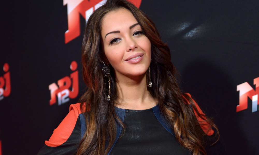 French TV hosts Nabilla Benattia poses during the presentation of her new NRJ12 TV show on October 21, 2013 at the NRJ group headquarters in Paris. AFP / PHOTO / ERIC FEFERBERG ERIC FEFERBERG / AFP