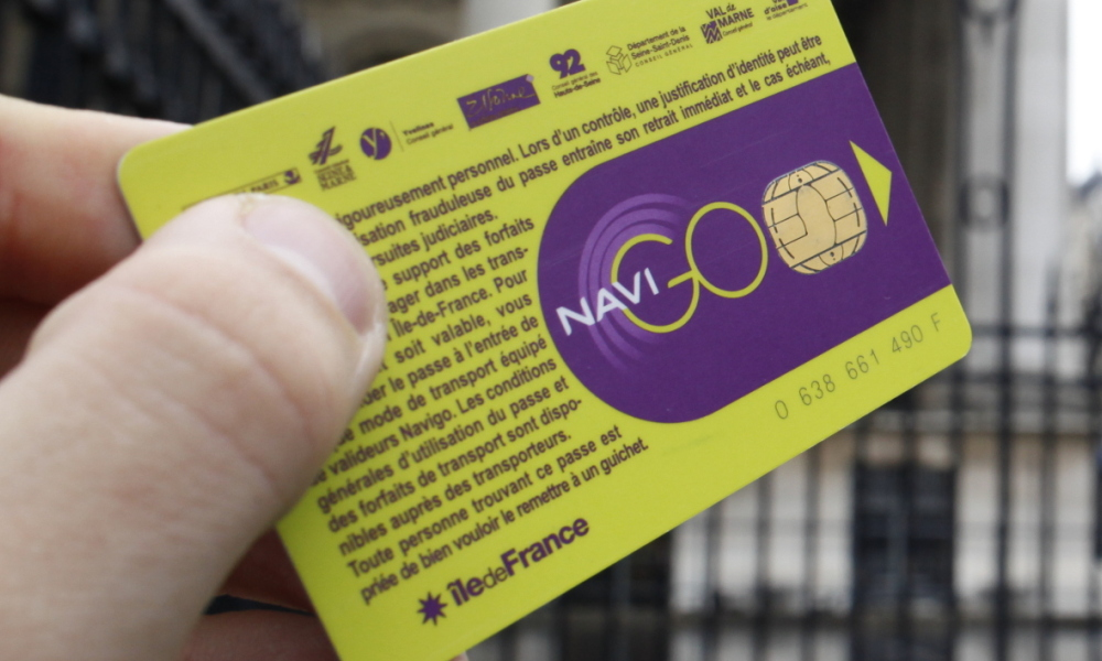 Passe Navigo - A person holds a Navigo pass in front of a metro station in Paris, on December 10, 2014. The Transport union of Ile-de-France (Stif) voted on December 10, 2014 to set up a single tariff of 70 euros for all public transports of Paris area. AFP PHOTO ELIOT BLONDET 