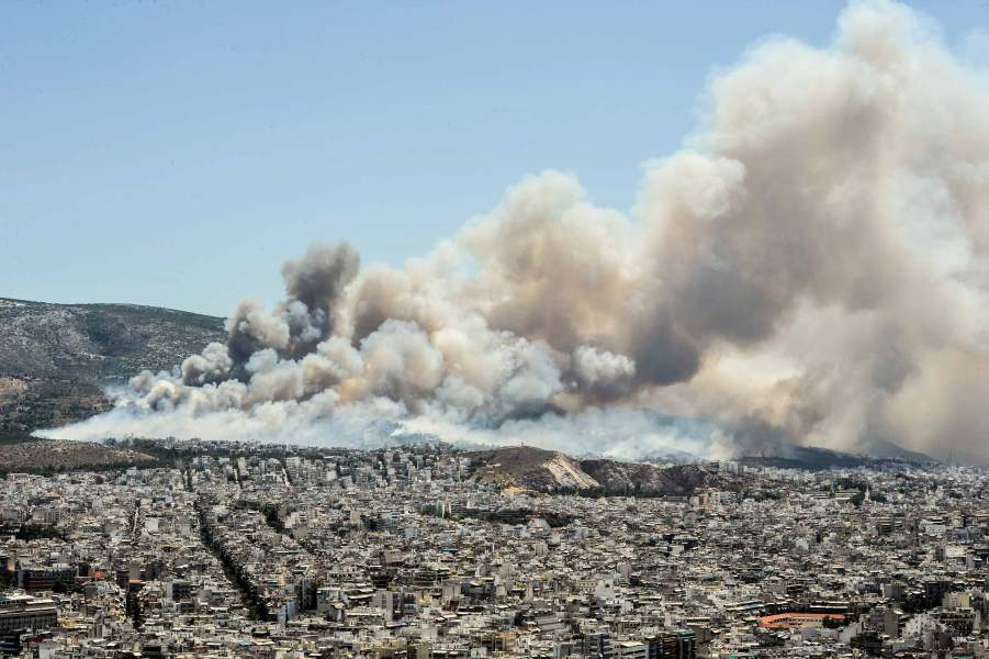 An helicopter of firefighters fly over smokes billowing over Athens, on July 17, 2015 as firemen were battling a brush fire in northeastern Athens and another wildfire in the southern Pelopponese peninsula that prompted the evacuation of five villages. More than 120 firefighters had been dispatched to the area, supported by 50 fire engines, four aircraft and two helicopters, officials said. AFP PHOTO / ANDREAS SOLARO
