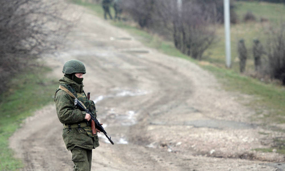 """Russian soldiers patrol the area surrounding the Ukrainian military unit in Perevalnoye, outside Simferopol, on March 20, 2014. Kiev will never recognise Russia's annexation of Crimea and will fight for the """"liberation"""" of the strategic Black Sea peninsula, Ukraine's parliament said in a resolution adopted on March 20. AFP PHOTO/ Filippo MONTEFORTE"""
