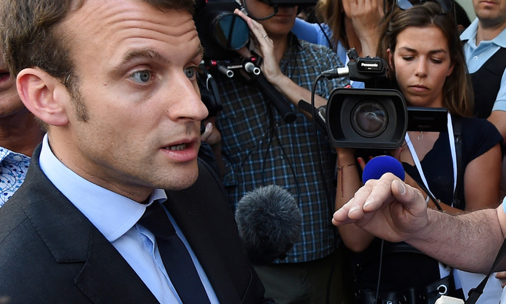 French Economy Minister Emmanuel Macron (L) speaks with protesters about the controversial government's labour reform, during a visit in Lunel on May 27, 2016.  SYLVAIN THOMAS / AFP