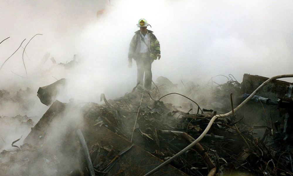 A fireman walks amongst the rubble and the smoldering wreckage of the World Trade Center 11 October 2001 in New York. An interfaith ceremony was held at ground zero in conjunction with the one month anniversary of the attacks, marked by the short prayer service and a moment of silence at 8:48am. AFP Photo/POOL/Gary Friedman GARY FRIEDMAN / LOS ANGELES TIMES / AFP