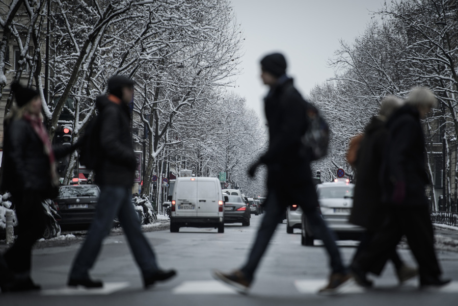 Pedestrians cross a street lined with snow-covered trees in Paris on February 7, 2018 following heavy snowfall.