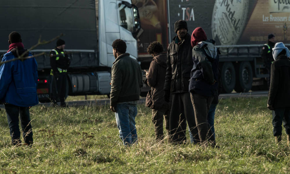 "A French gendarme faces migrants as he guards a truck after migrants tried to mount several trucks on the A16 motorway near the site of the Eurotunnel in Coquelles, near Calais, northern France on January 21, 2016. Approximately 300 migrants have tried to board trucks protected by French police, according to an estimate made by an AFP photographer at the scene. Clashes already erupted briefly on the night of January 20 at the port bypass Calais between several hundred migrants and security forces, who fired tear gas to restore the situation, according to an AFP correspondent. These incidents occurred after the prefecture of Pas-de-Calais had set an ultimatum which expired early in the afternoon for the last migrants to leave a deforested 100 metre strip of the ""Jungle"" camp along the ring road for safety reasons."