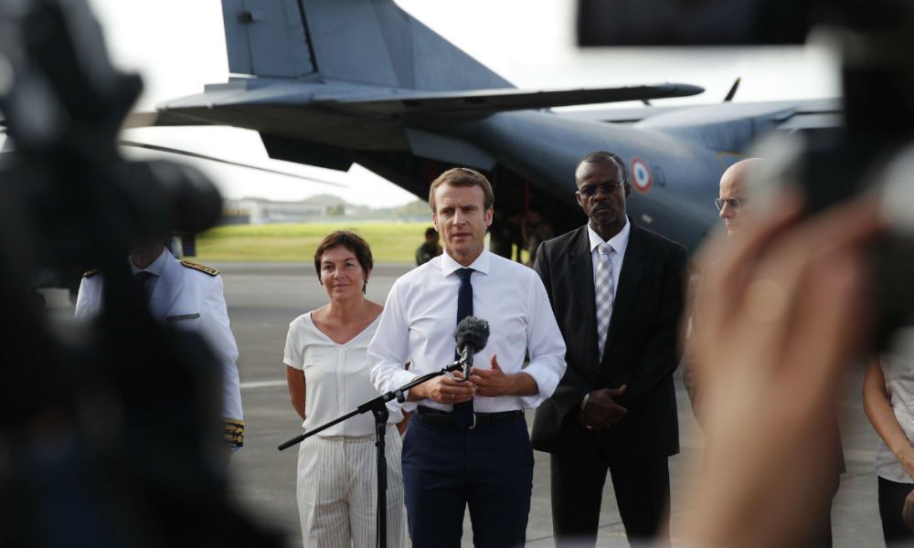 France's President Emmanuel Macron (C), next to French Overseas Minister Annick Girardin (L), addresses the media upon his arrival in Pointe-a-Pitre, Guadeloupe island, the first step of his visit to French Caribbean islands on September 12, 2017.  Christophe Ena / AFP