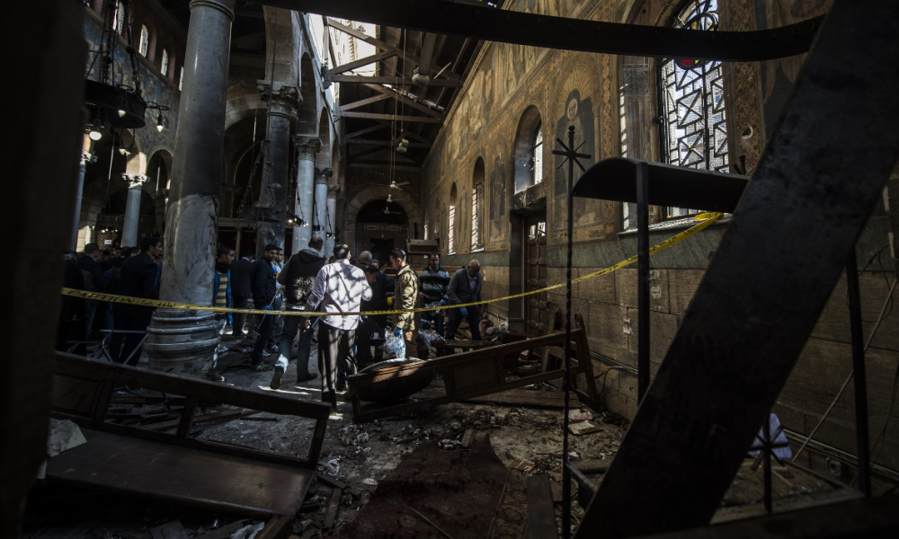 Egyptian security forces inspect the scene of a bomb explosion at the Saint Peter and Saint Paul Coptic Orthodox Church on December 11, 2016, in Cairo's Abbasiya neighbourhood. The blast killed at least 25 worshippers during Sunday mass inside the Cairo church near the seat of the Coptic pope who heads Egypt's Christian minority, state media said. KHALED DESOUKI / AFP