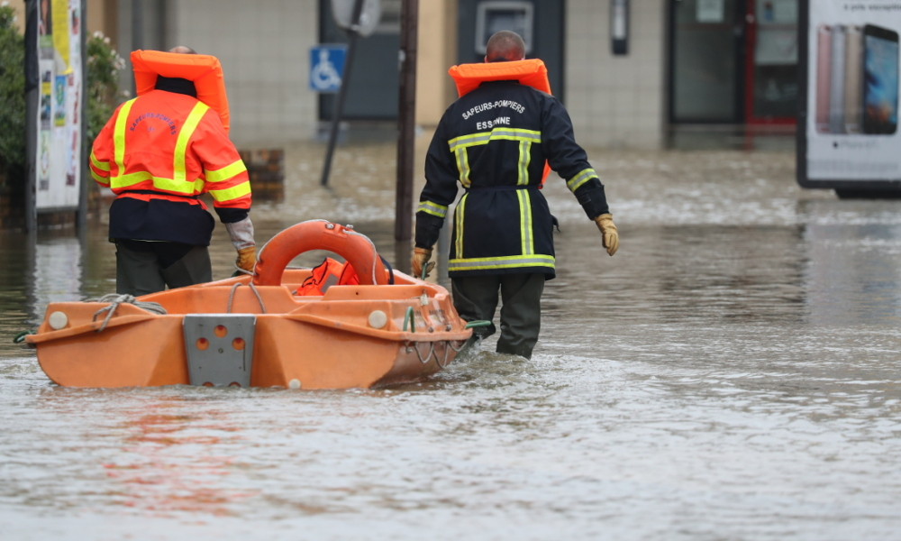 Firefighters push their small boat in a flooded street after the Yvette river burst its banks and forced residents to be evacuated in Longjumeau, some 20kms south of Paris, on June 2, 2016.