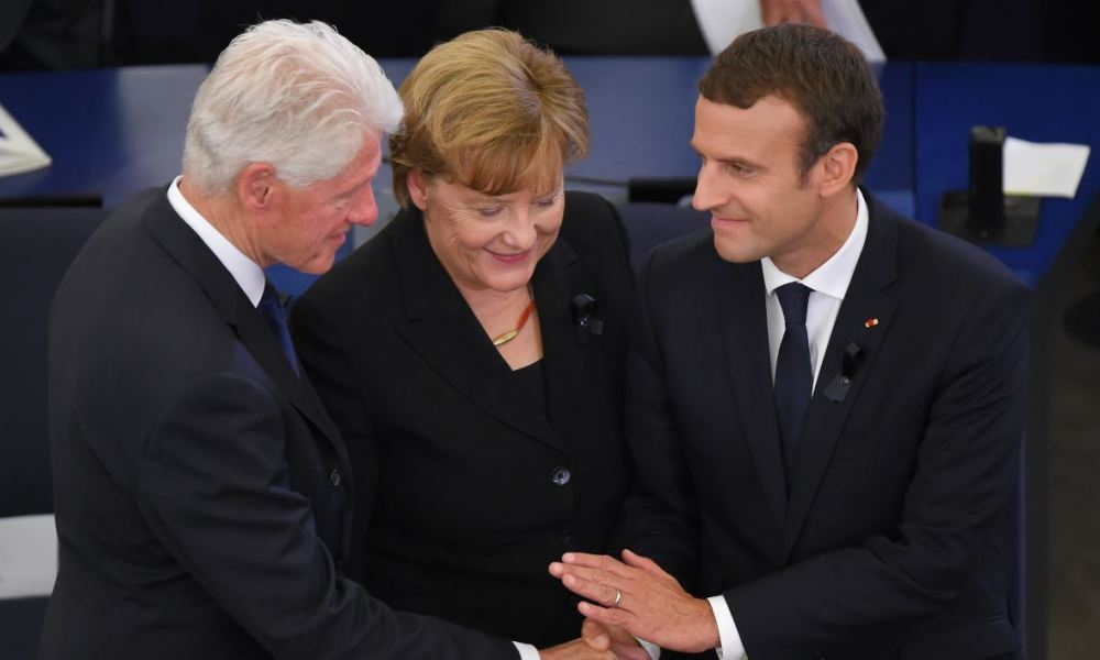 (L-R) Former US president Bill Clinton, German Chancellor Angela Merkel and French President Emmanuel Macron shake hands during a ceremony for late German Chancellor Helmut Kohl at the European Parliament in Strasbourg, eastern France, on July 1, 2017. Kohl, who oversaw German reunification and was a driving force in Europe's integration, died on June 16 at age of 87. PATRICK HERTZOG / AFP