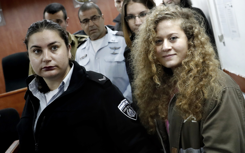 Seventeen-year-old Palestinian Ahed Tamimi (R), a well-known campaigner against Israel's occupation, arrives for the beginning of her trial in the Israeli military court at Ofer military prison in the West Bank village of Betunia on February 13, 2018.