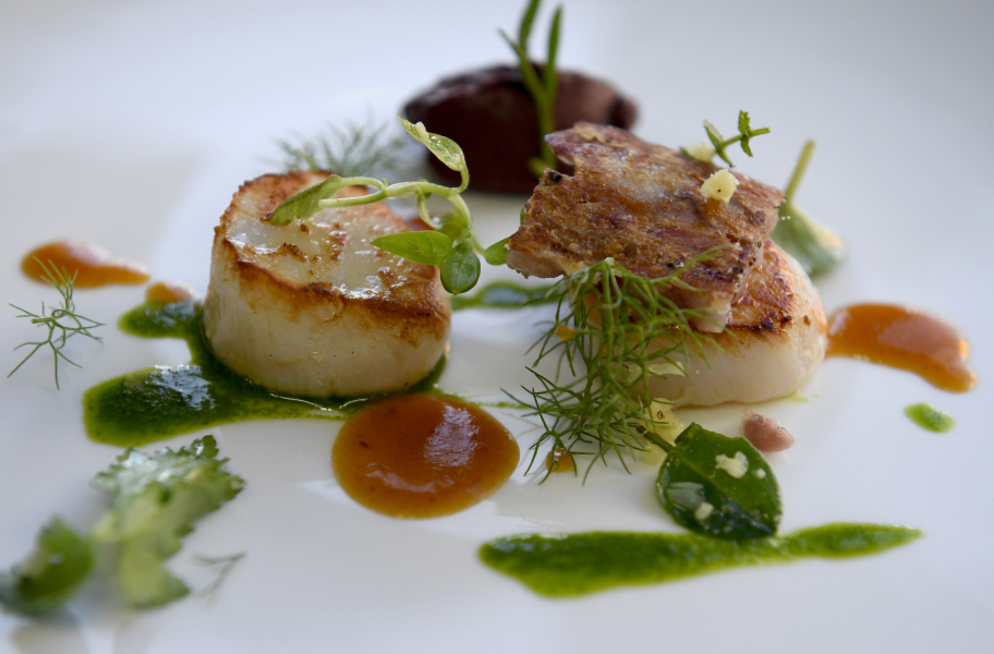 """This picture taken on January 25, 2018 shows a dish of """"tripier marin"""", seared scallops with black pudding (boudin noir) and pig's feet broth garnished with glasswort and watercress by French chef Olivier Bellin at """"L'auberge des Glazicks"""" in Plomodiern, western France.  FRED TANNEAU / AFP"""