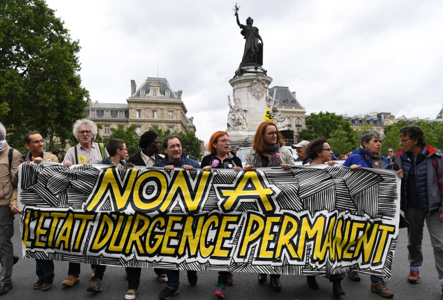"""People hold a banner reading """"no to the permanent state of emergency"""", during a demonstration against the state of emergency on Place de la Republique (Republic's Square) on July 1, 2017, in Paris.  ALAIN JOCARD / AFP"""
