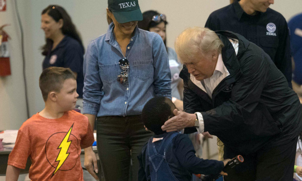 US President Donald Trump and First Lady Melania Trump listen to children, victims of Hurricane Harvey, at NRG Center in Houston on September 2, 2017.  NICHOLAS KAMM / AFP