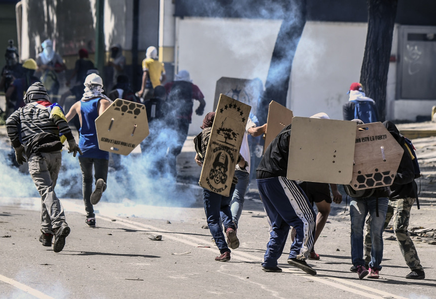 Opposition activists clash with riot police during a protest against President Nicolas Maduro's government and in defiance of a new ban on rallies ahead of Sunday's controversial vote in Caracas on July 28, 2017.