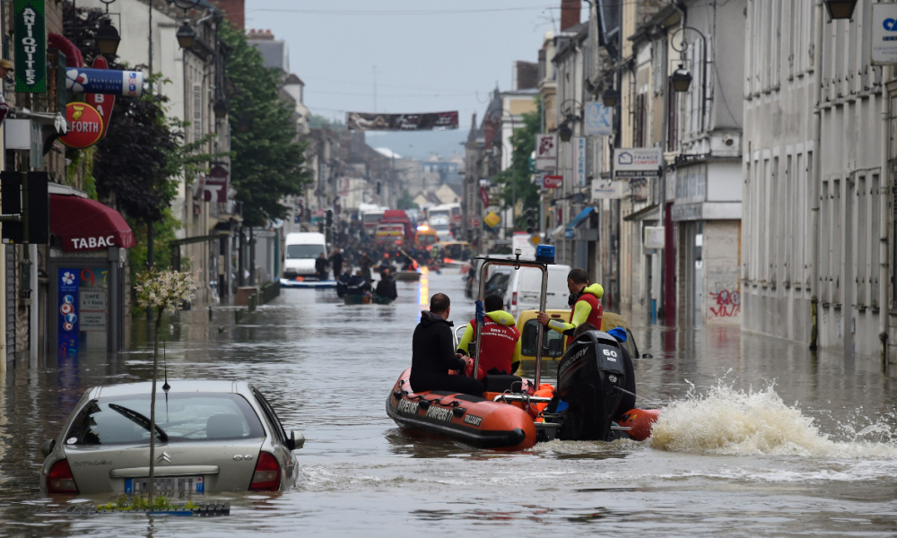Rescuers ride a boat during a rescue operation in a flooded area of Nemours, some 80km south of Paris, on June 1, 2016. Incessant rain in regions of Germany, France and Austria led to flash flooding June 1, forcing residents to seek refuge on rooftops and stranding hundreds of pupils at their school overnight, authorities said. In Paris, many promenades along the Seine were closed due to high water while in Nemours, 80 kilometres (50 miles) to the south, residents had to be evacuated in the afternoon after the Loing river burst its banks. AFP PHOTO / DOMINIQUE FAGET  DOMINIQUE FAGET / AFP
