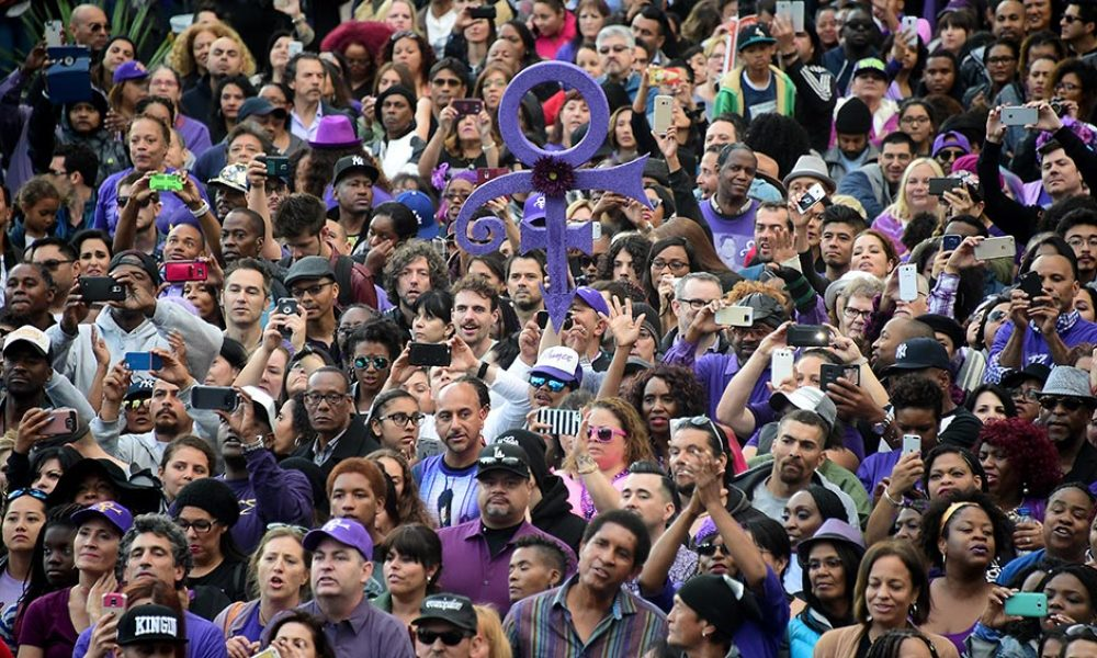"This file photo taken on May 6, 2016 shows an estimated 5,000 Prince fans, wearing purple and black, attend a tribute concert outside Los Angeles City Hall in Los Angeles, California. The state of Minnesota on June 7, 2016 celebrated ""Prince Day,"" with residents encouraged to wear the music legend's signature color purple on what would have been his 58th birthday. Minnesota Governor Mark Dayton, in a proclamation making June 7 this year Prince Day, hailed the chart-topping singer for his ""revolutionary music and iconic identity."""