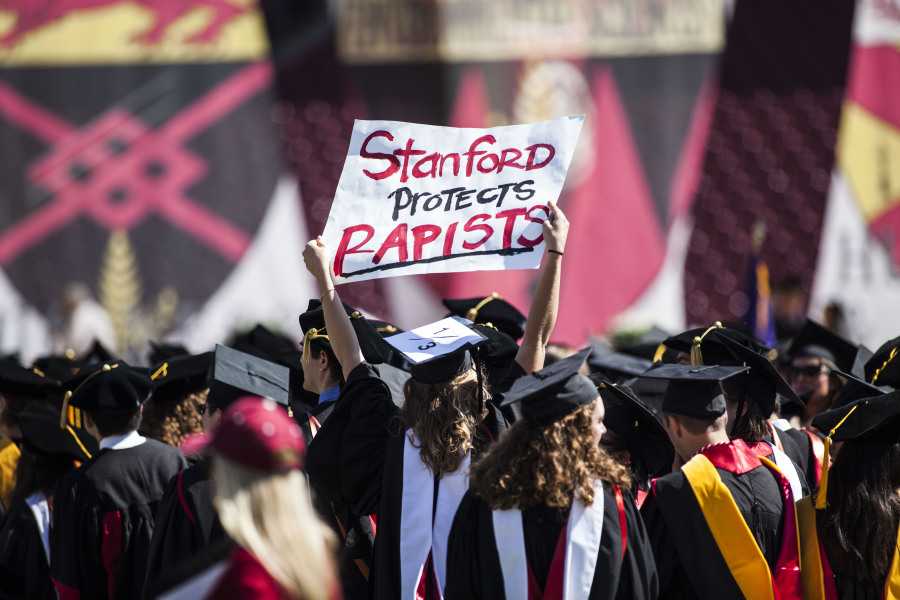 STANFORD, CA - JUNE 12: Graduating student, Andrea Lorei, who help organize campus demonstrations holds a sign in protest during the 'Wacky Walk' before the 125th Stanford University commencement ceremony on June 12, 2016 in Stanford, California.