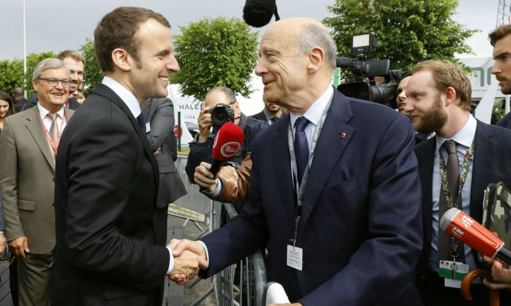 French Economy Minister Emmanuel Macron (L) shakes hands with former French Prime Minister and presidential candidate of the opposition Republicans (Les Republicains, or LR) for the French presidental elections in 2017, Alain Juppe (R) on June 16, 2016 at the Eurosatory 2016 defence and security international exhibition in Villepinte.  PATRICK KOVARIK / AFP