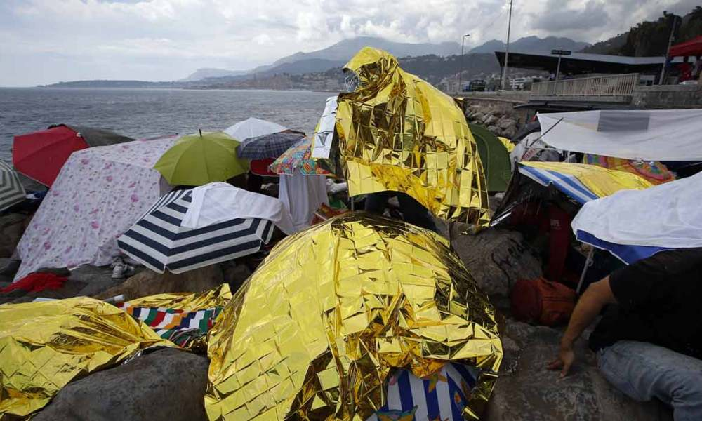 Des migrants se protègent de la pluie à Vintimille en Italie (photo d'illustration)