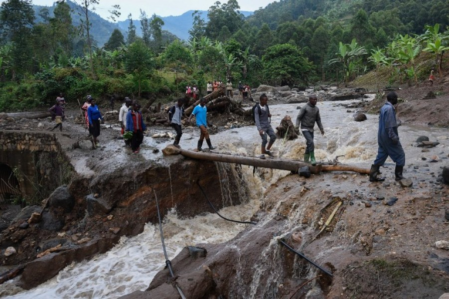 People cross the Sume river on October 12, 2018, a day after it burst its banks in the eastern village of Nanyinza, in Uganda's Bududa district. At least 34 people were killed after the river in eastern Uganda burst its banks, sending thick sludge and rocks barrelling into homes, disaster officials said. Isaac Kasamani / AFP
