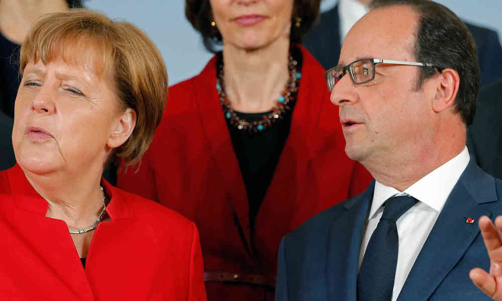 German Chancellor Angela Merkel (L) talks with French President Francois Hollande as they pose for a family photo for the 18th Franco-German cabinet meeting in Metz, eastern France, on April 7, 2016.  vincent kessler / POOL / AFP