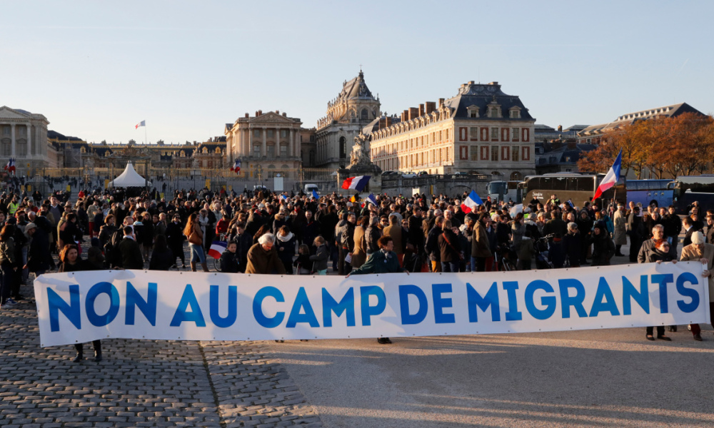 "Protestors hold a banner reading ""No to the migrants camp"" during a demonstration on November 11, 2016 in Versailles, southern Paris against a temporary migrant camp project in Louveciennes.  FRANCOIS GUILLOT / AFP"